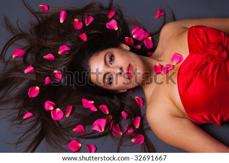 Beautiful brunette woman in a red dress lying down with pink rose petals in her hair. - stock photo