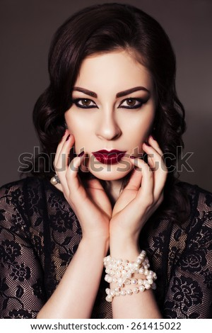 Beautiful brunette woman in black dress with evening make up and waves retro  hairstyle. fashion posing - stock photo