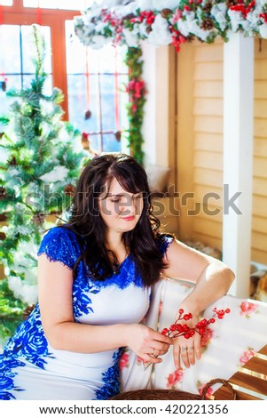 Beautiful brunette woman in blue and white dress, in the hands of Kalina winter, sitting on a bench near the Christmas tree on the background of the New year - stock photo