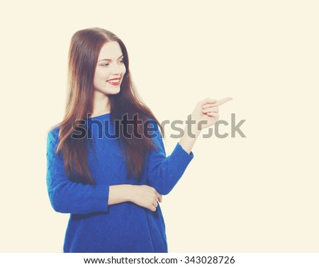 Beautiful brunette woman in blue sweater pointing at copy space retro toning - stock photo
