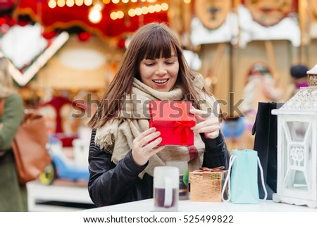 beautiful brunette woman  in scarf holding a present box on a christmas market