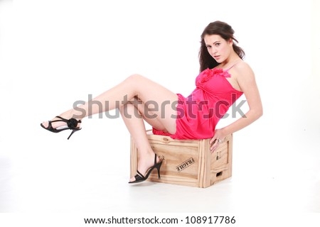 Beautiful brunette woman in sexy pink dress and black high heel stillettos sitting on wooden box crate seductively - stock photo