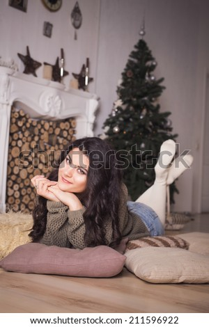 Beautiful brunette woman in shorts and sweater in new year decorated interior with christmas tree in it. Indoors - stock photo
