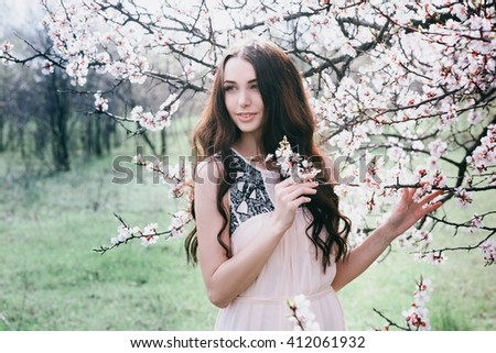 Beautiful brunette woman in the park standing near the blossom tree on a warm summer day,lifestyle - stock photo