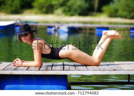 Beautiful brunette woman laying on pier with black hat and swimsuit