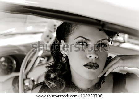 Beautiful Brunette woman looking out of a car window with dice hanging in the windshield