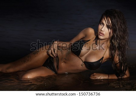 Beautiful brunette woman lying and relaxing on the beach. - stock photo