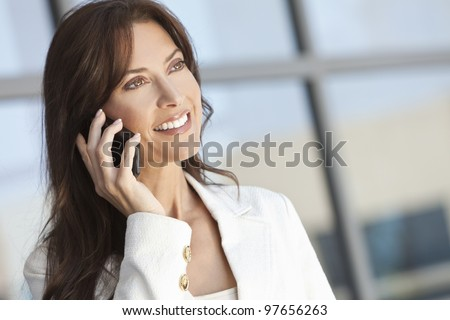 Beautiful brunette woman or businesswoman in her thirties talking on a cell phone. - stock photo