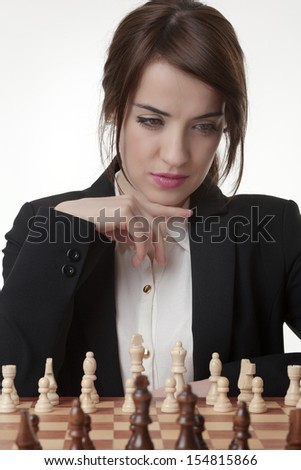 Beautiful Brunette Woman Playing Chess - stock photo
