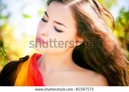 beautiful brunette woman portrait in nature, wind in hair, eyes closed, summer day