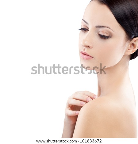 beautiful brunette woman portrait with hand on naked shoulder, half-turn view - stock photo