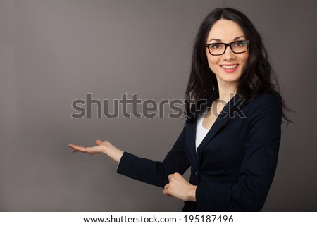 beautiful brunette woman presenting copyspace over grey background - stock photo