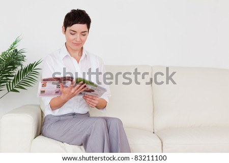 Beautiful brunette woman reading a magazine in a waiting room - stock photo