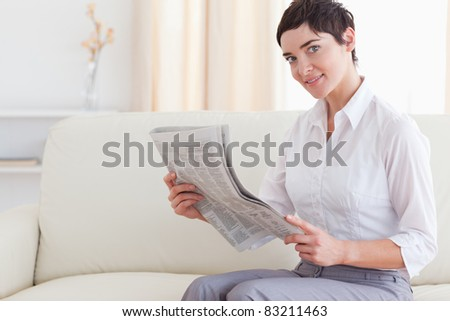 Beautiful brunette woman reading the news in the living room