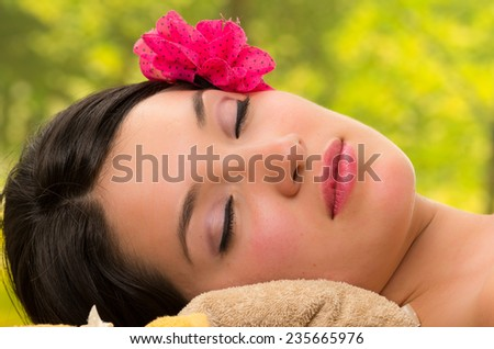 beautiful brunette woman relaxing lying down in outdoor spa with eyes closed - stock photo