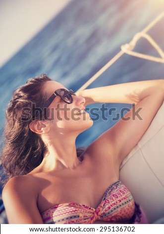 Beautiful brunette woman relaxing on sailboat, sitting on the deck and enjoying bright sun light, luxury summer vacation on water transport - stock photo