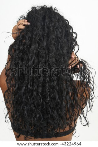 Beautiful brunette woman showing off her long curly hair on white background. Not isolated - stock photo