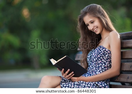 Beautiful brunette woman sits on bench and read book on city street - stock photo