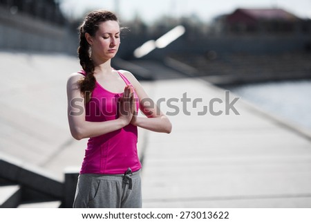 beautiful brunette woman sitting in yoga pose at the beach - stock photo