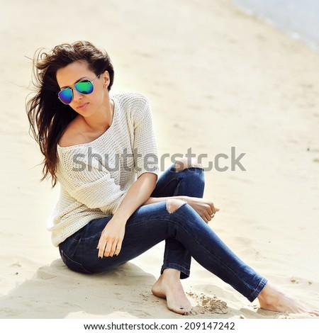 Beautiful brunette woman sitting on a sand  - stock photo