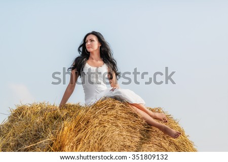 Beautiful brunette woman sitting on hay bale in warm summer day - stock photo