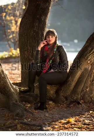 Beautiful brunette woman sitting under big tree at autumn park - stock photo
