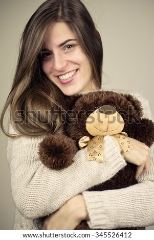 Beautiful brunette woman smiles with her teddy bear. Color effects and custom white balance are used on this picture. - stock photo