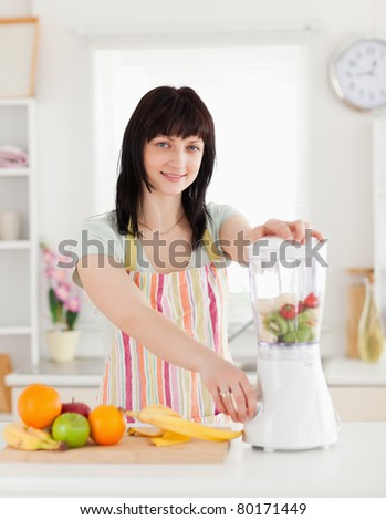 Beautiful brunette woman using a mixer while standing in the kitchen