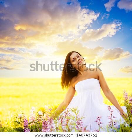 beautiful brunette woman walking in a field at sunset - stock photo