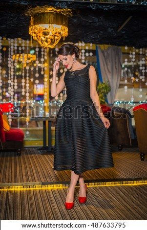 stock-photo-beautiful-brunette-woman-walking-in-the-restaurant-in-black-dress-and-red-shoes-smiling-with-her-487633795