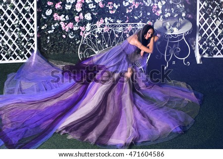 Beautiful brunette woman wearing long purple dress sitting on the bench in a flower garden