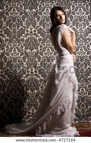 beautiful brunette woman wearing white blouse and skirt on background with pattern