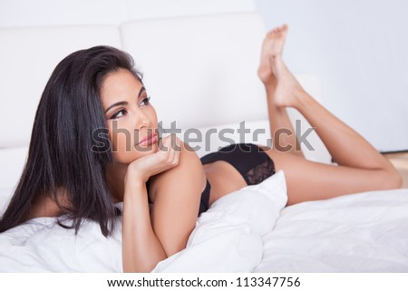 Beautiful brunette woman with a lovely smile relaxing on her stomach on her bed with her chin resting in her hands - stock photo