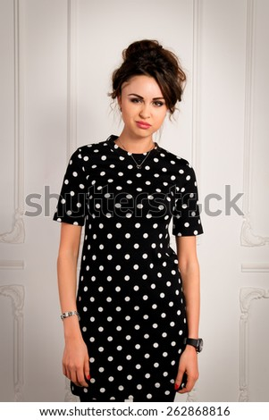 Beautiful brunette woman with angry expression in a black dress in studio - stock photo