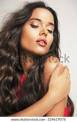 Beautiful brunette woman with beauty long curly hair and bright makeup. Fashion model with wavy hairstyle. Toned in warm colors. Studio shot, Vertical - stock photo