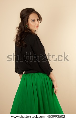 Beautiful brunette woman with black blouse and green skirt - stock photo