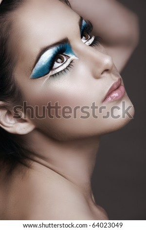 Beautiful brunette woman with cat eyes make-up in bright blue and white. - stock photo