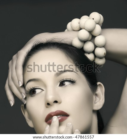 beautiful brunette woman with classic make-up and wooden beads on her hand in vintage finish - stock photo