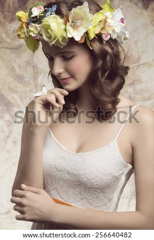 Beautiful, brunette woman with colorful makeup, wreath of flowers on head, little bird on her finger and wearing white dress. - stock photo