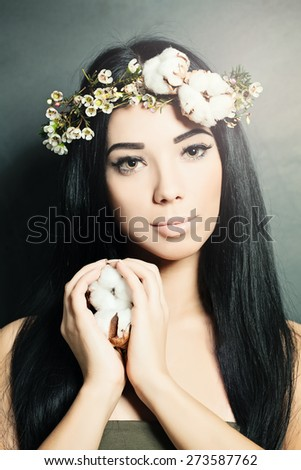 Beautiful brunette woman with cotton flowers in her hair and hand. Fashion photo - stock photo