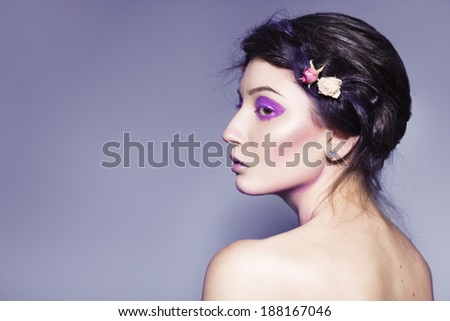 Beautiful brunette woman with creative make up and dead roses in braid hairstyle with her back on us - stock photo
