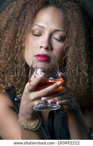 Beautiful brunette woman with curl hair feels red wine aroma emanating holding the cup in his hands
