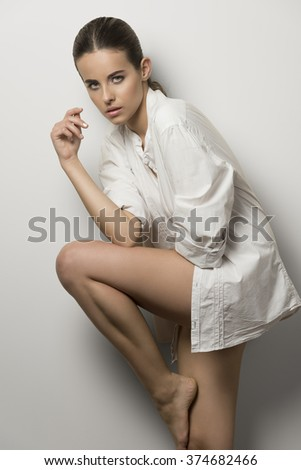 beautiful brunette woman with delicate make-up, wearing unbuttoned shirt and nude legs. In fashion pose she is looking in camera with charming expression  - stock photo