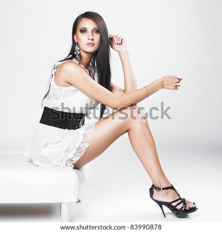Beautiful brunette woman with elegant white dress. Fashion photo