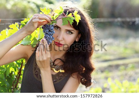 Beautiful brunette woman with grape in vineyard - stock photo