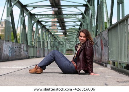 Beautiful brunette woman with leather jacket sitting on a bridge with graffiti