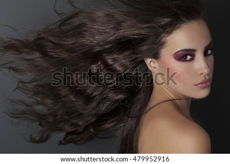 beautiful brunette woman with long flying hair and beauty makeup