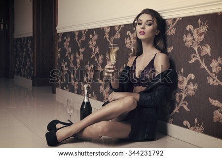 beautiful brunette woman with sexy lingerie, heels and open fashion jacket sitting on floor taking a glass of champagne in hand. Ready for sexy new year toast  - stock photo