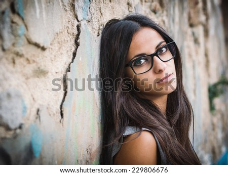 Beautiful brunette woman with sunglasses over a ruinous wall - stock photo