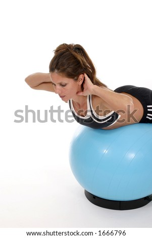 Beautiful brunette woman working out using an exercise ball.  Shot isolated on white background. - stock photo